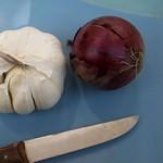 Küchenbrett mit Messer, Zwiebel und Knoblauch